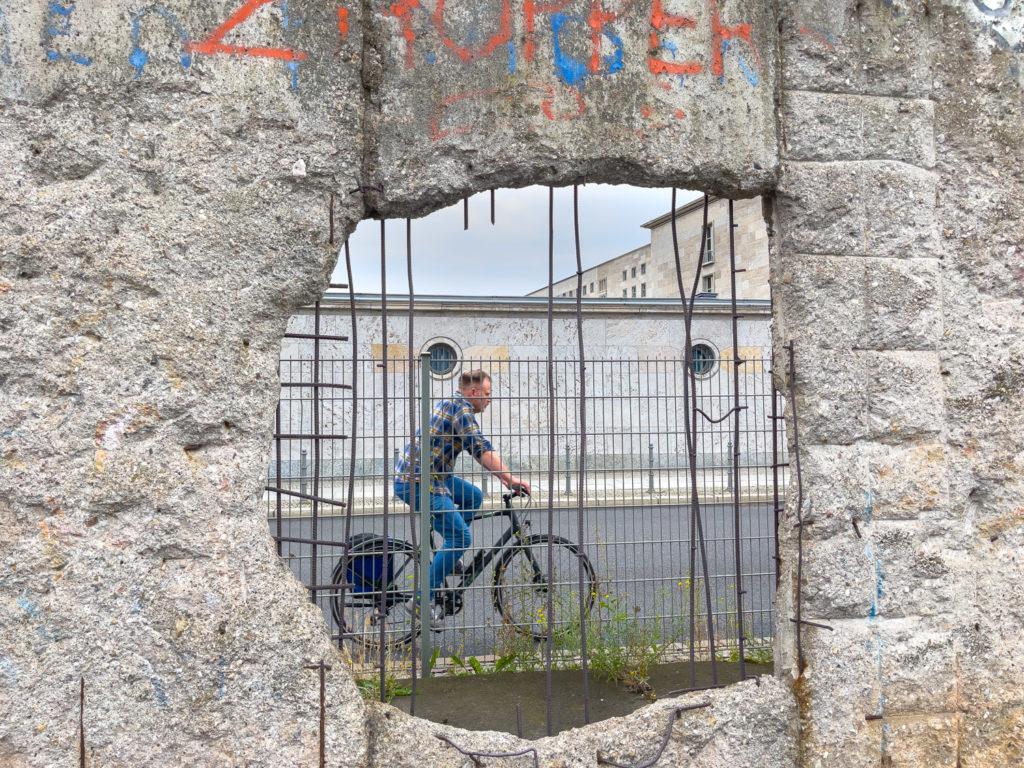 Cycliste à travers le mur de Berlin