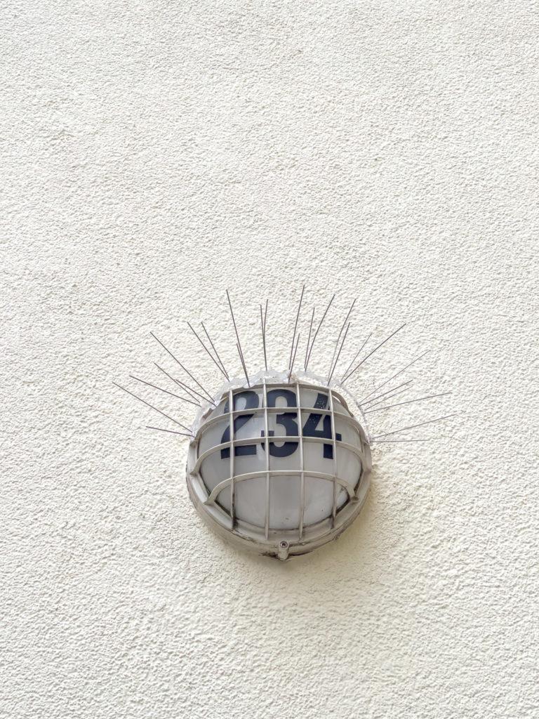 Lampe d'un immeuble avec système anti pigeon