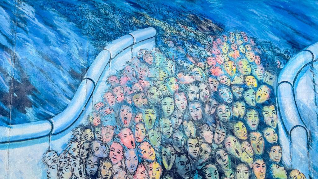 Personnes qui passent le mur de Berlin au format street art