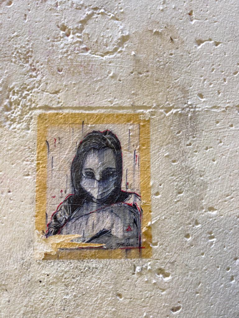 Visage d'une fille masquée sur le mur de Berlin